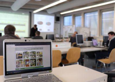 Impression vom Workshop: Ein Computerbildschirm im Seminarraum zeigt eine Ansicht des Computerspiels Ecopolicy. Im Hintergrund sind Workshop-Teilnehmer zu sehen.