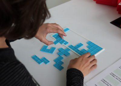 Kind beim Lösen eines Rätsels mit geometrischen Formen aus 3D-Druck.