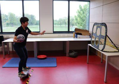 InnoSÜD-Mitarbeiterin auf dem Balance-Brett vor einer Handball-Torwand, im Begriff zu schießen.