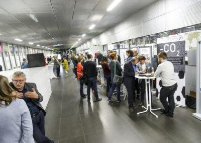Menschen im Gespräch an Infoständen beim Marktplatz im Foyer der Hochschule.