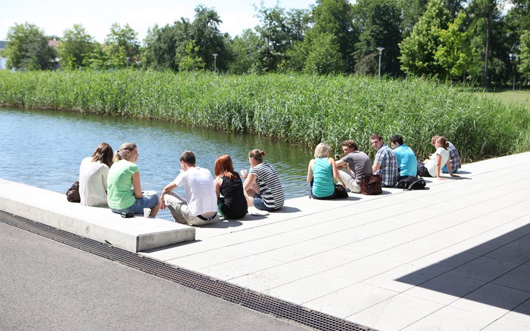 Junge Menschen sitzen am See der Hochschule Neu-Ulm.