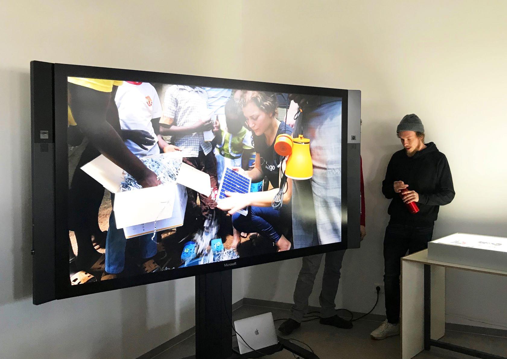 Bildschirm während einer Präsentation. Der Bildschirm zeigt eine Frau, die eine Solarzelle hält.