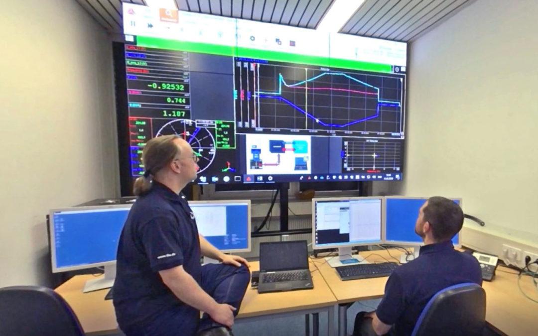 Standbild aus dem Video: Zwei Wissenschaftler vor einer Bildschirmwand mit Messwerten im Smart Grid Labor.