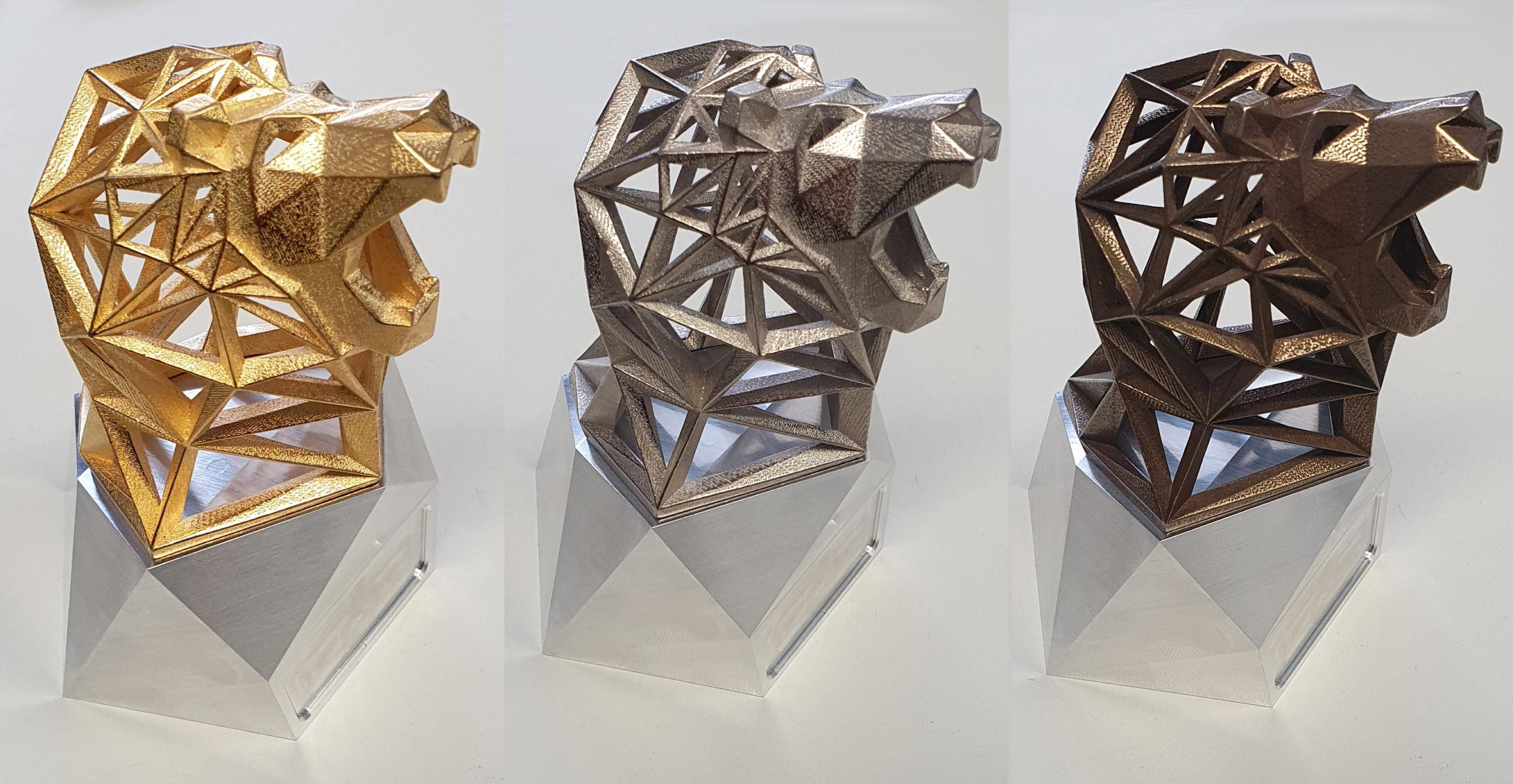 Die Trophäen in Gold, Silber und Bronze. Jede Trophäe zeigt den Kopf eines brüllenden Löwen in geometrischer Gitterform.